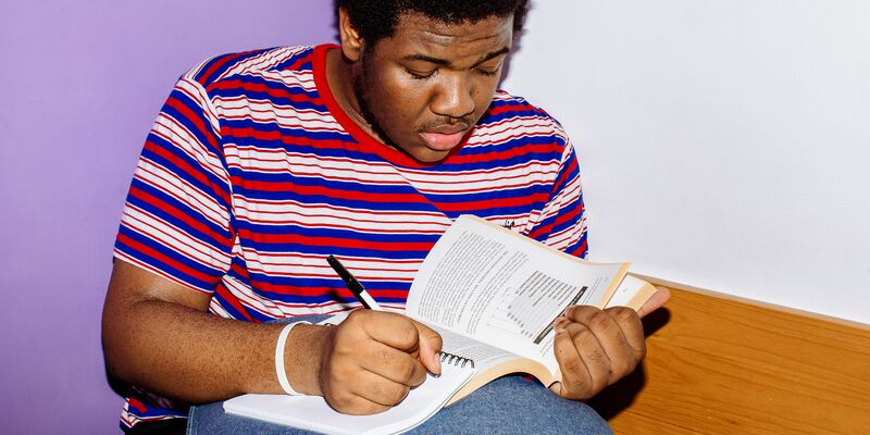 Student sat on a chair writing in a book