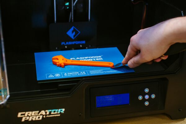 A bright orange 3d printed adjustable spanner on the bright blue bed of a 3d printer