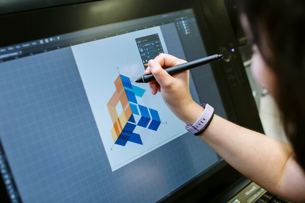 Female student designs graphic on wacom tablet