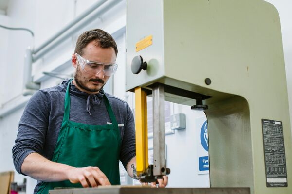 Male student uses sawing tool in workshop