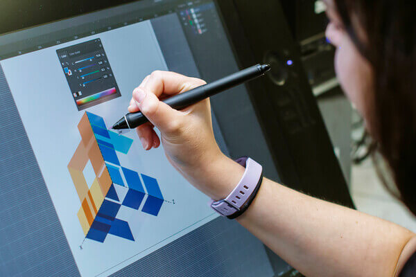 A student drawing a geometric design on a Wacom tablet screen