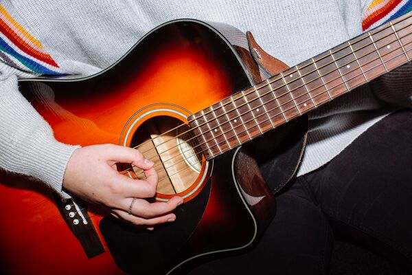 Close up of student strumming the guitar