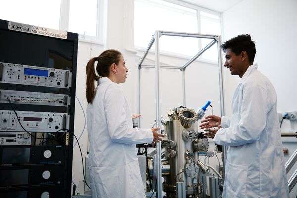 Two students converse in the Molecular Beam Epitaxy Laboratory