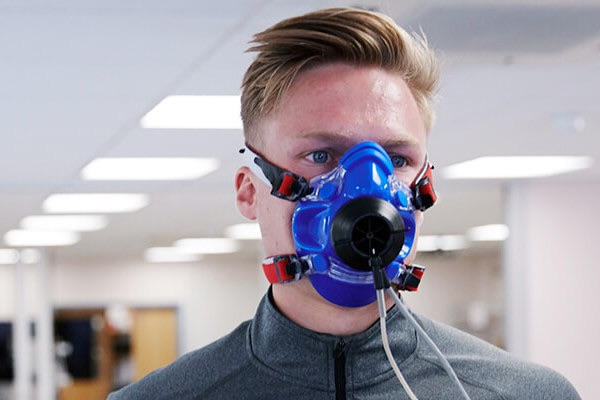male student running on treadmill with breathing mask on