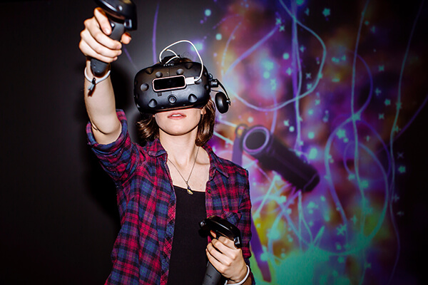 Student using a HTC Vive virtual reality headset and controls before a digital projection.