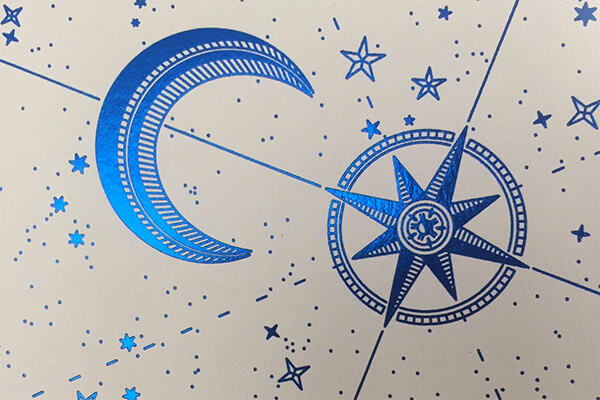 A blue foil design on white textured paper featuring a crescent, compass and scattered stars