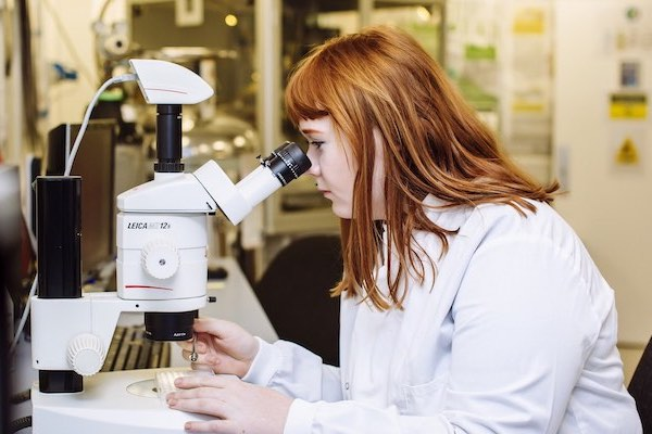 Female scientist looking through a microscope in the lab
