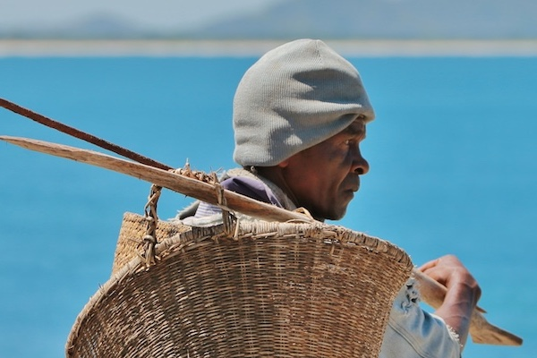 man with a wicker basket by the sea