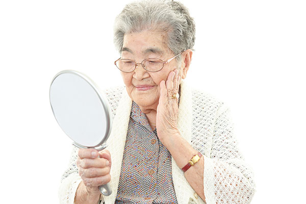 An elderly person examining their face in a handheld mirror