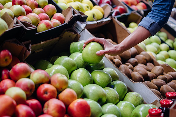 A hand touching an apple amongst a variety of others in a market stall