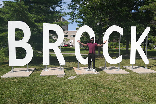 Sports student in front of Brock University sign in Canada