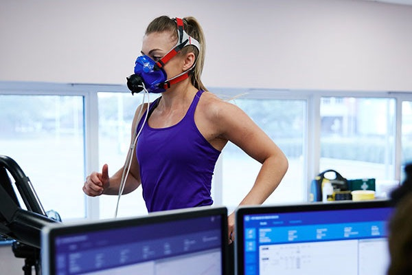 female in sports clothes running on treadmill for health sciences experiment