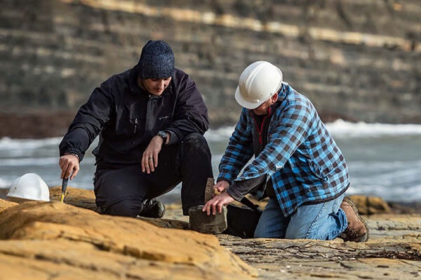 two palaeontologists looking for fossils on the beach