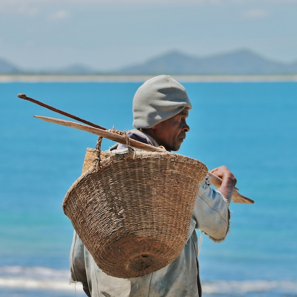 Fisherman holding his catch and rods by tropical sea shore