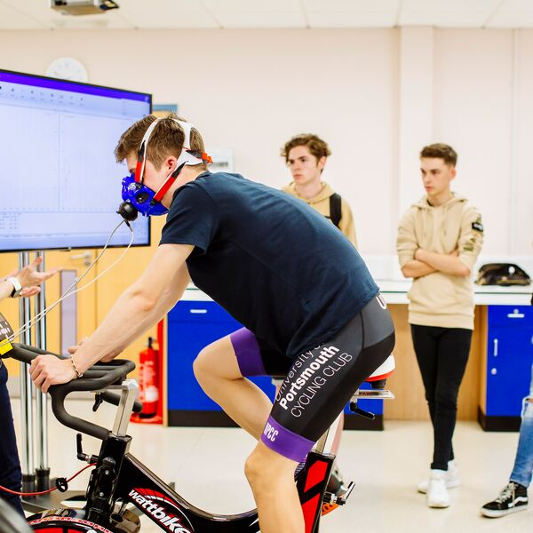 male student training on stationary bike