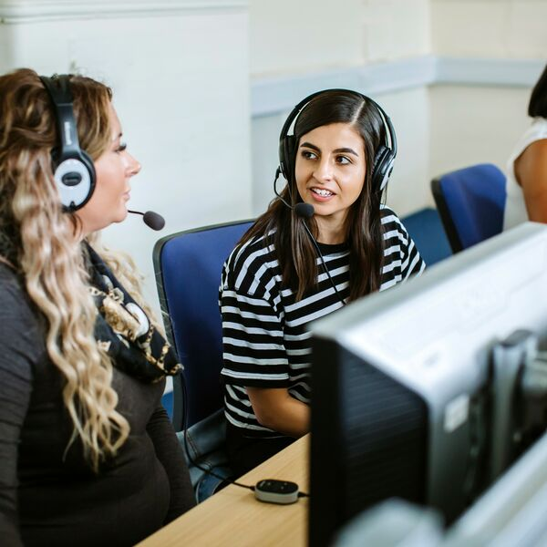 two female students speaking with headsets