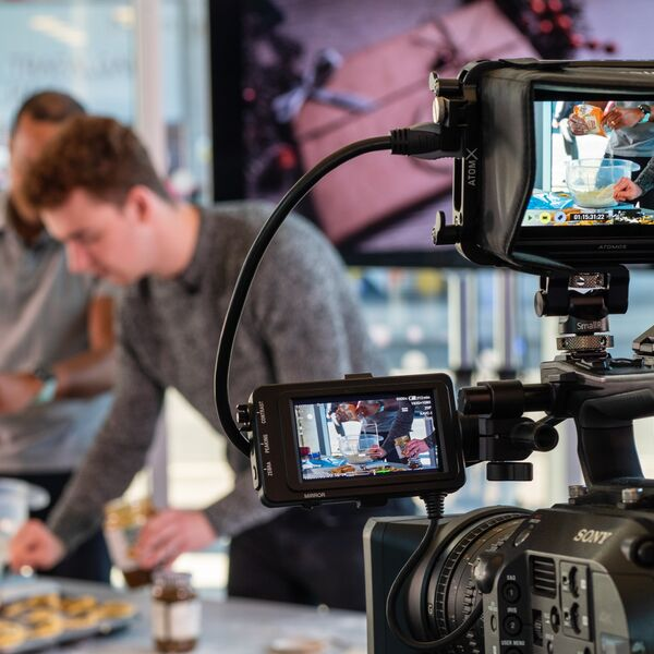 A video camera recording two people presenting a cookery programme in Eldon foyer