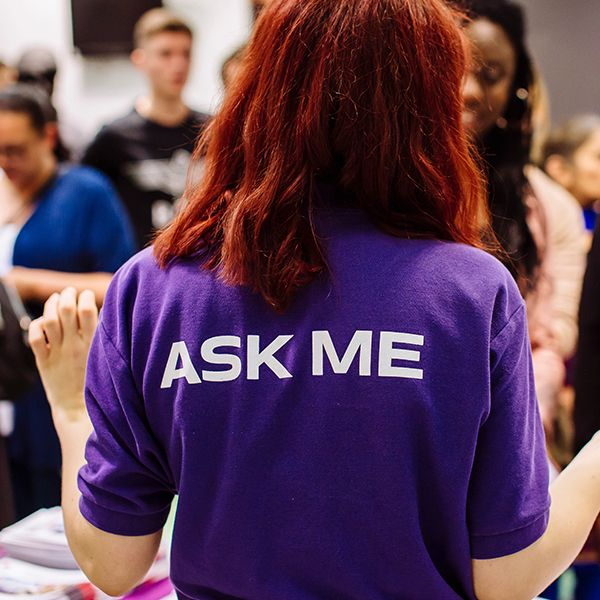"Student ambassador wearing purple ""Ask me"" shirt at open day"