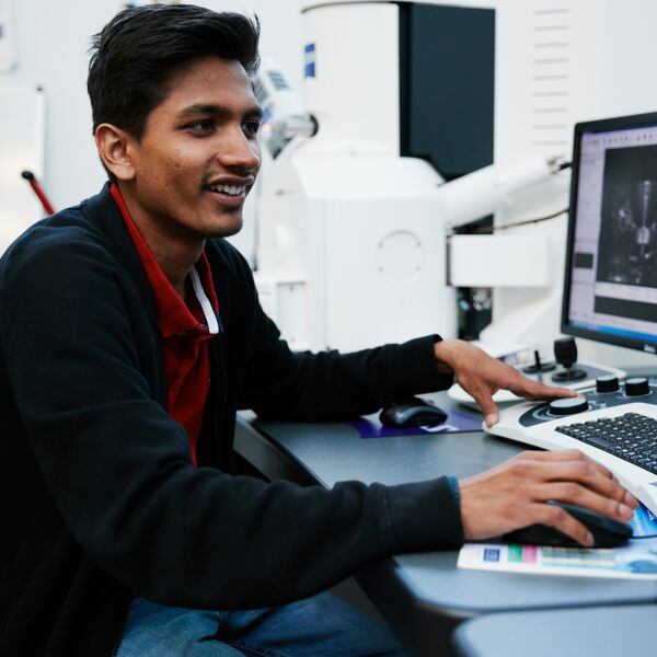 Male student smiling and working on computer in facility