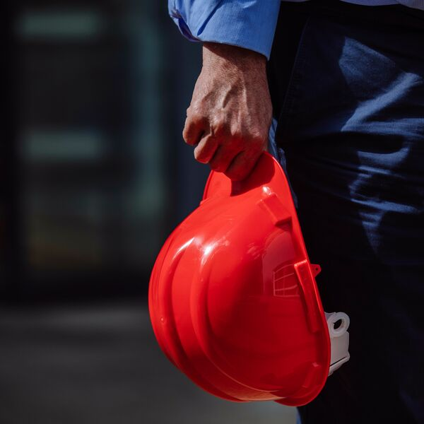 Male worker holding red hard hat at building site