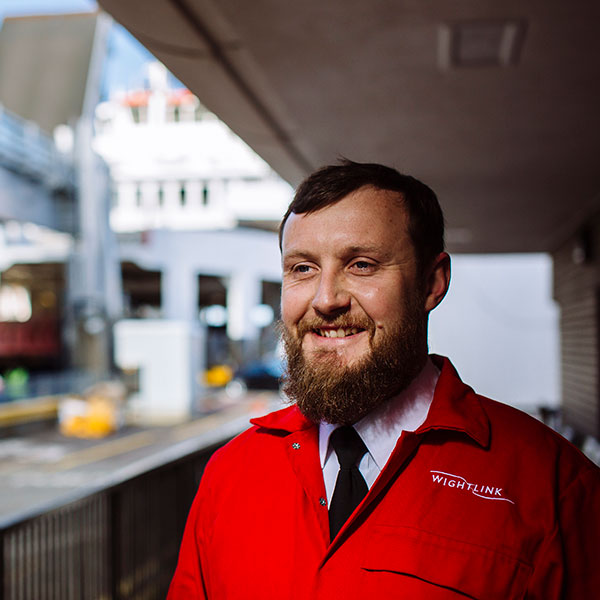 Young man with beard in a red Wightlink jacket smiling confidently at the camera