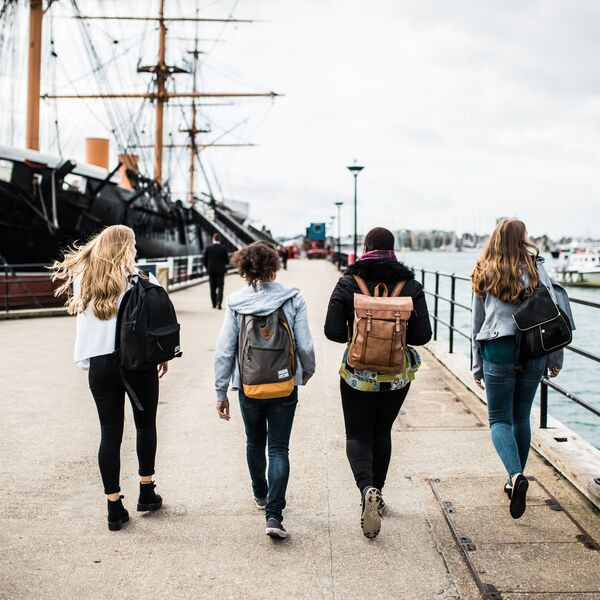 4 students walking towards a boat