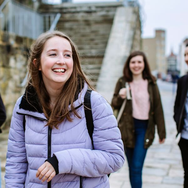 A group of friends smiling and laughing, walking through old portsmouth
