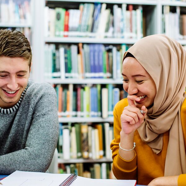 Students in the library studying, smiling and laughing
