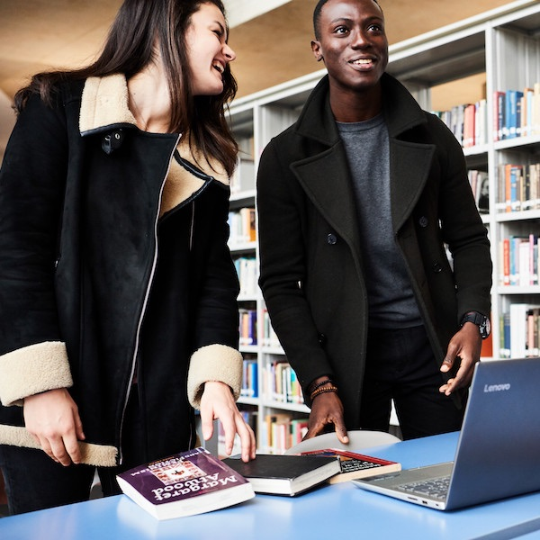 female and male student in library