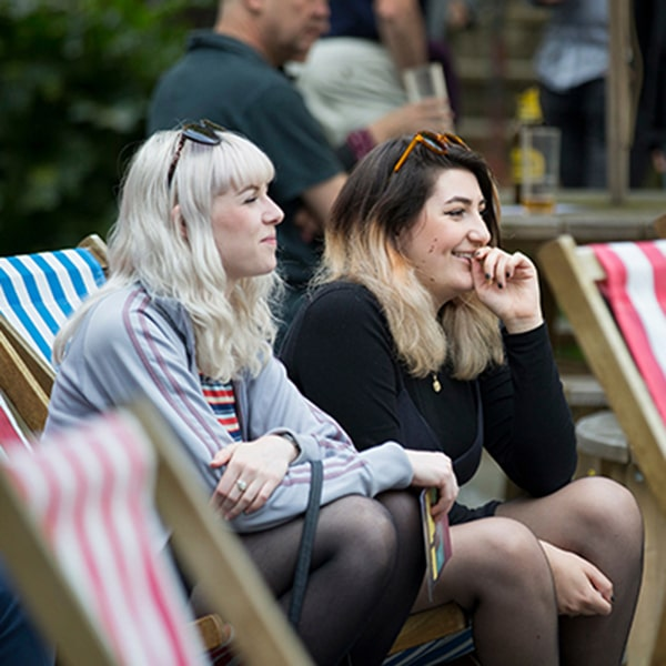 Two females sitting in giant deck chairs at Students' Union