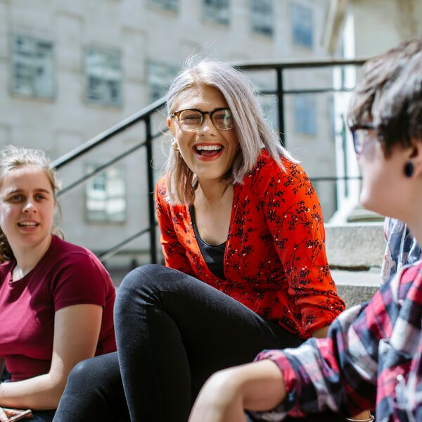 Female University of Portsmouth students sitting on stairs outside