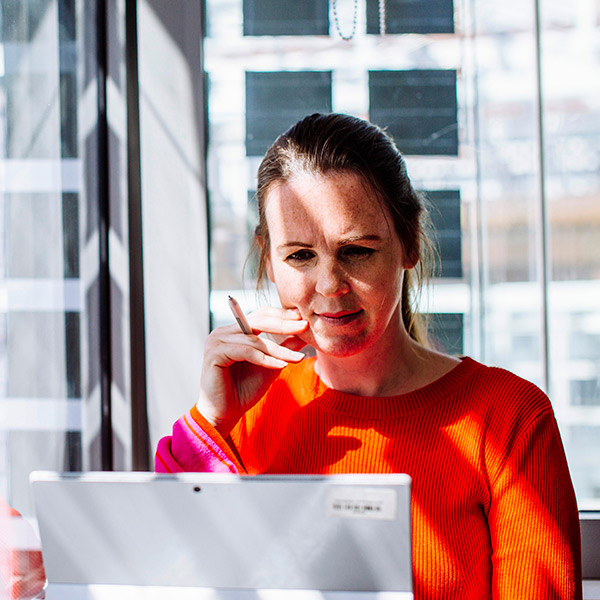 Woman in red jumper working at desk