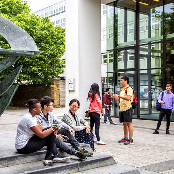 Students chatting outside Dennis Sciama Building, Portsmouth