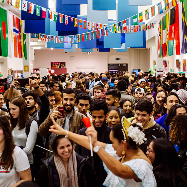 Students celebrating in Festival of Cultures in hall draped with different flags