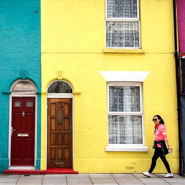 Student walking down Southsea street past colouful houses