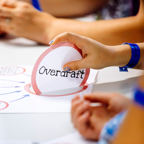A hand holding an 'Overdraft' popup sign from a diagram on a desk