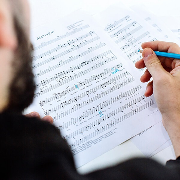 Person marking sheet music with light blue pencil