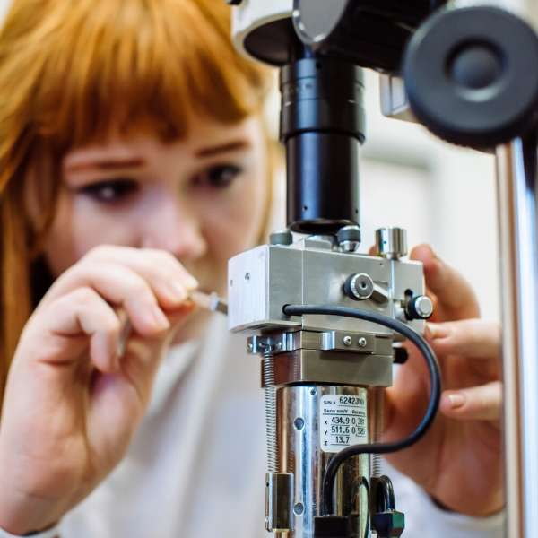 Researcher carries out maintenance on microscopic equipment