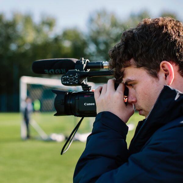 Young male student filming football match