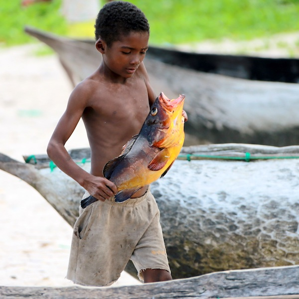 Young boy with a just-caught fish, Madagascar
