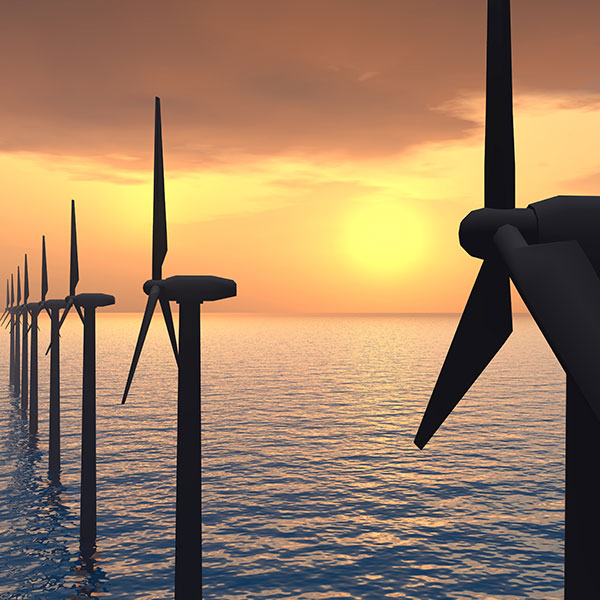Offshore wind turbines rise out of the water in front of a sunset
