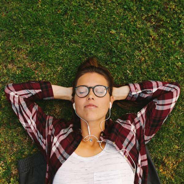 Female student relaxing on grass with headphones in