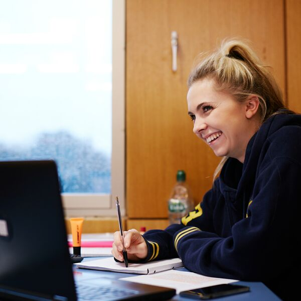 Female student smiling while studying in the library