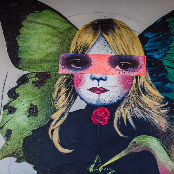 Wall graffiti of a blonde woman with butterfly wings and collaged eyes