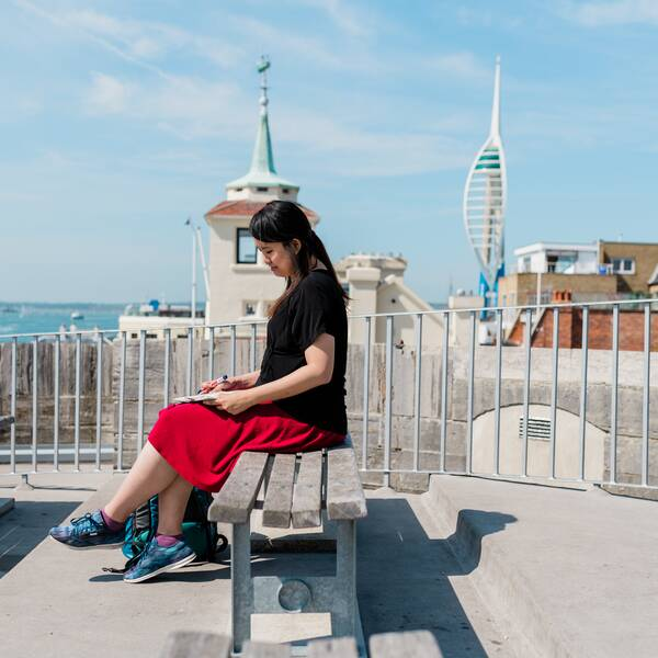 Female international student sat outside in Southsea