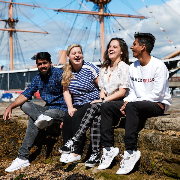 Four University of Portsmouth students laughing at historic dockyard