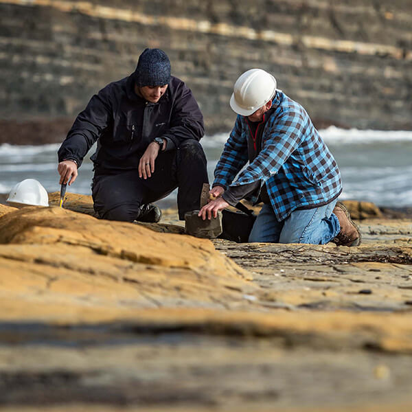 Student and tutor examining rocks on coast