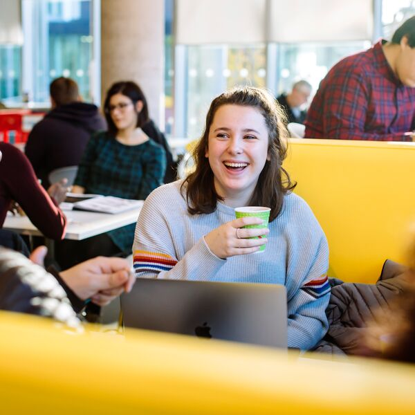 Students laughing with coffee sitting on yellow sofas