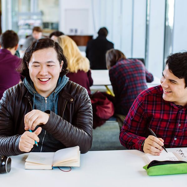 Two male students laughing while studying