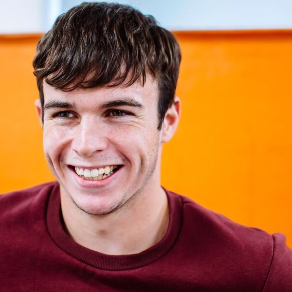 Male UoP student smiling in front of orange wall